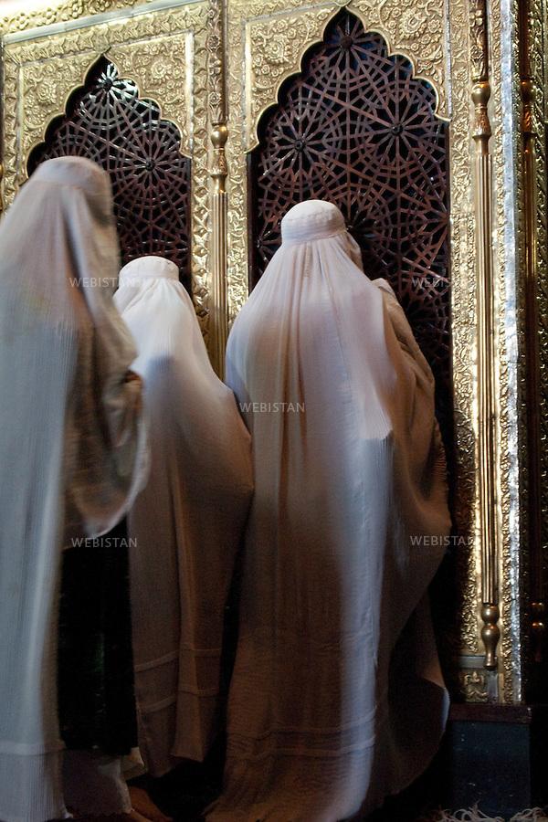 """AFGHANISTAN - MAZAR-E CHARIF - 7 aout 2009 : .Le nom de Mazar-e Charif signifie """"sanctuaire sacre"""" et fait reference au sanctuaire et a la mosquee qui auraient ete batis, selon les afghans chiites comme sunnites, sur le tombeau de l'imam Ali. Ancien lieu de culte paien puis boudhiste, le sanctuaire de Mazar-e Charif est aujourd'hui le plus grand centre de pelerinage musulman en Afghanistan. Son activite culmine a l'occasion du nouvel an afghan, le 21 mars de chaque annee...Mosquee de Mazar-e Charif, femmes afghanes se recueillant devant le reliquaire de l'imam Ali. ..AFGHANISTAN - MAZAR-E CHARIF - August 7th, 2009 : The name Mazar-e Charif means """"sacred sanctuary"""" and refers to the sanctuary and mosque which were built, according to Sunni and Shiite Afghans alike, over the tomb of the Imam Ali. An ancient religious site for Pagans and then Buddhists, today the Mazar-e Charif sanctuary is the Muslim pilgrimage centre of Afghanistan. Activity here culminates annually on March 21, Afghan New Year..Mazar-e Charif mosque. Afghan women in worship before the shrine of Imam Ali."""