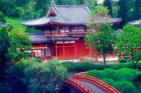 Close-up of authentic Byodo-in Buddhist temple on windward Oahu, surrounded by lush green foliage and charming red bridge