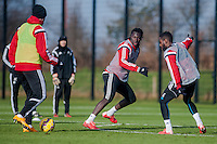 SWANSEA, WALES - JANUARY 28:   Bafetibis Gomis of Swansea City ( centre ) looks to defend the ball during training on January 28, 2015 in Swansea, Wales.