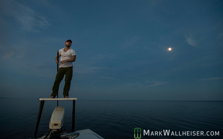 Michael Tolbert poles for redfish under a full moon on the flats at Shell Point with Justin Wallheiser.