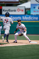 Rochester Red Wings first baseman Zander Wiel (12) waits for a throw as Billy Burns (17) runs up the base line during an International League game against the Scranton/Wilkes-Barre RailRiders on June 25, 2019 at Frontier Field in Rochester, New York.  Rochester defeated Scranton 10-9.  (Mike Janes/Four Seam Images)