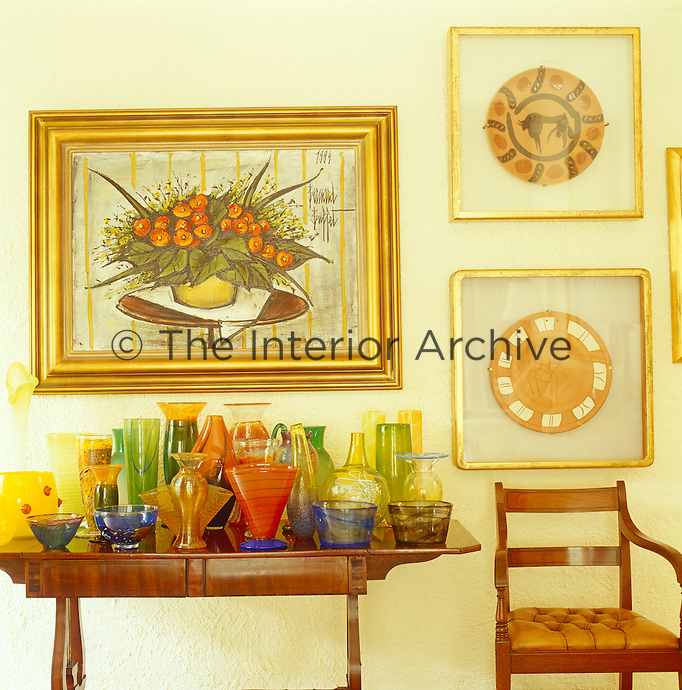 In this living room a collection of vividly coloured Murano glass is grouped on a table under a collection of gilt-framed paintings