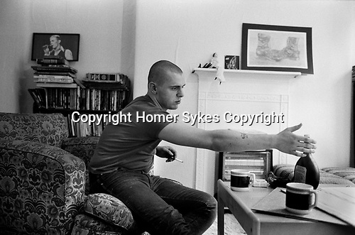 Skinhead Jimmy John ( 19yrs ) 1980 at home in Tower Hamlets east London Uk. He had a French girl friend and is drinking Mateus rose wine very popular at the time. The drawing on the mantle is by him. He worked as a hospital refuse porter at Royal London Hospital Whitechapel. Ex punk, ex rocker, not a member of the NF, he carries a knife.