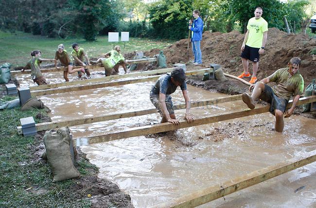 Participants climb through mud at the Mud Run near Commonwealth Stadium in Lexington, Ky., on Saturday, September 22, 2012. Photo by Tessa Lighty | Staff