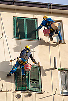 Milano, periferia nord, ristrutturazione della facciata di un palazzo. Imbianchini lavorano sospesi da funi --- Milan, north periphery, renovation of a building's facade. Painters suspended from ropes