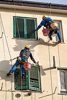 Milano, periferia nord, ristrutturazione della facciata di un palazzo. Imbianchini lavorano sospesi da funi --- Milan, north periphery, renovation of a building's facade. Painters suspended from ropes