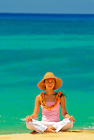 Young woman sitting on the beach in lotus position