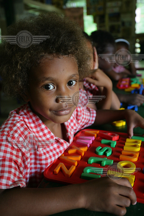 4 year old Nathan plays with an ABC puzzle at the YWCA Kindergarten, an early child development centre in Honiara.