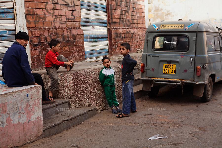 Algerie. Oran. 09 Avril 2011.Scene de rue. Une homme et des enfants devant une ancienne Renault 4L utilitaire. Sur le mur, un tag &quot;Karim&quot; en arabe.<br /> <br /> <br /> Algeria, Oran. April 9th 2011<br /> Street scene. A man and some kids in front of an old Renault 4L S.U.V.. On the wall, a tag that says &ldquo;Karim&rdquo; in Arabic.