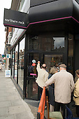 Depositors queue to withdraw their savings from a branch of the Northern Rock bank  in north London.