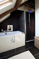 In the bathroom mosaic tiling and smooth stone add interesting textures to the simple black and white colour scheme