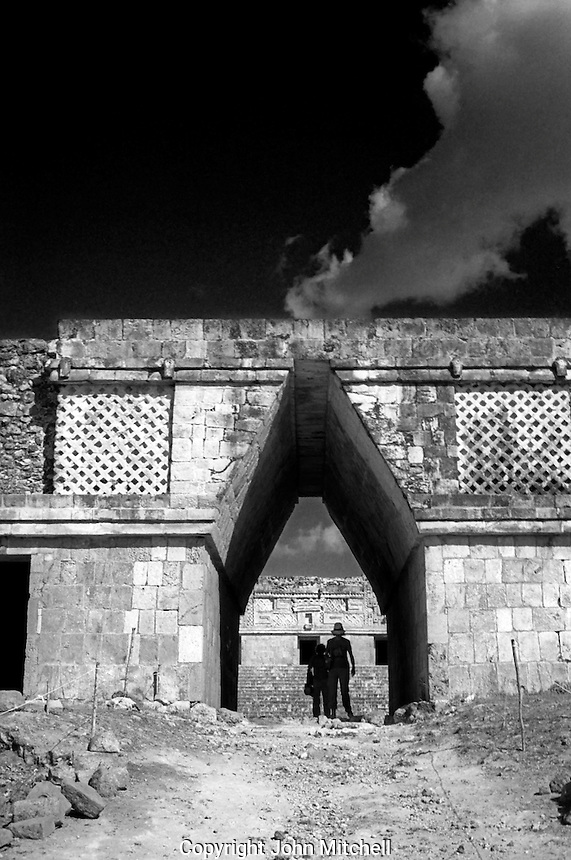 Woman and child standing beneath a Mayan corbeled arch in the Nunnery, Uxmal, Yucatan, Mexico