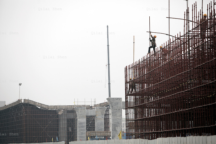 A worker operates  on a elevated highway construction site in Shanghai, China on 07 April, 2009.  China has undergone a major road building project as an investment in basic infrastructure and a cornerstone in economic development, linking cities by highways and vowing to extend its road network to every village in the country. More than 33,000 kilometers (20,500 miles) of highways have been built in the last five (5) years and China is on track to top the U.S. in terms of roadways...