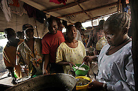 Mary Ngobeh serves lunch at the 'City of Rest', a rudimentary counselling and mini rehabilitation centre for recovering drug addicts, alcoholics and traumatised or delinquent youths.  Mary is the wife of the pastor who runs the centre and who attributes the centre's success to extensive rest, food and prayer. © Fredrik Naumann Freetown, Sierra Leone.