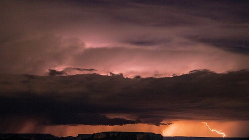 A late evening thunder and lightning storm hovers over the Grand Canyon in Arizona