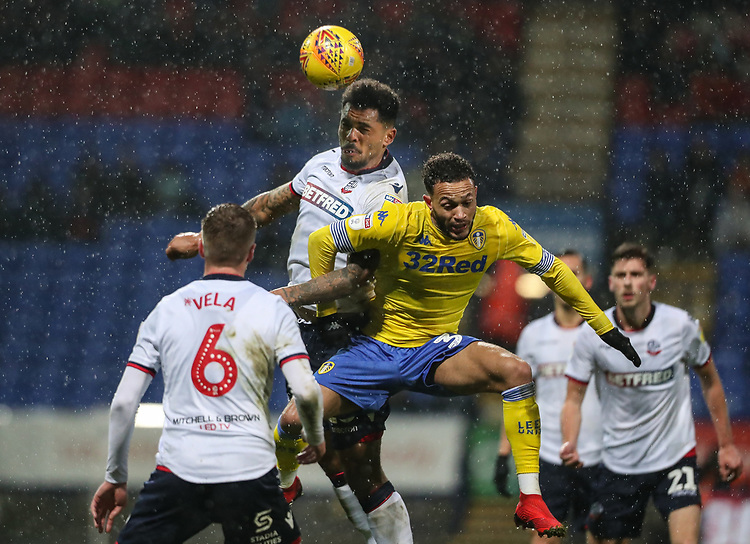 Bolton Wanderers' Josh Magennis competing with Leeds United's Lewis Baker<br /> <br /> Photographer Andrew Kearns/CameraSport<br /> <br /> The EFL Sky Bet Championship - Bolton Wanderers v Leeds United - Saturday 15th December 2018 - University of Bolton Stadium - Bolton<br /> <br /> World Copyright © 2018 CameraSport. All rights reserved. 43 Linden Ave. Countesthorpe. Leicester. England. LE8 5PG - Tel: +44 (0) 116 277 4147 - admin@camerasport.com - www.camerasport.com