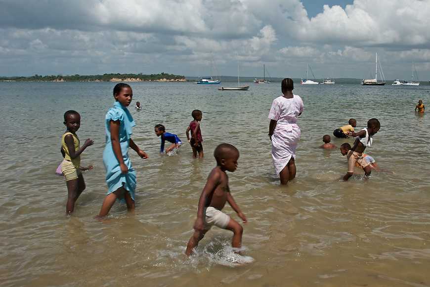 Children from a private school take a mid-day trip to the public beach near the Tanga Yacht Club to cool off.