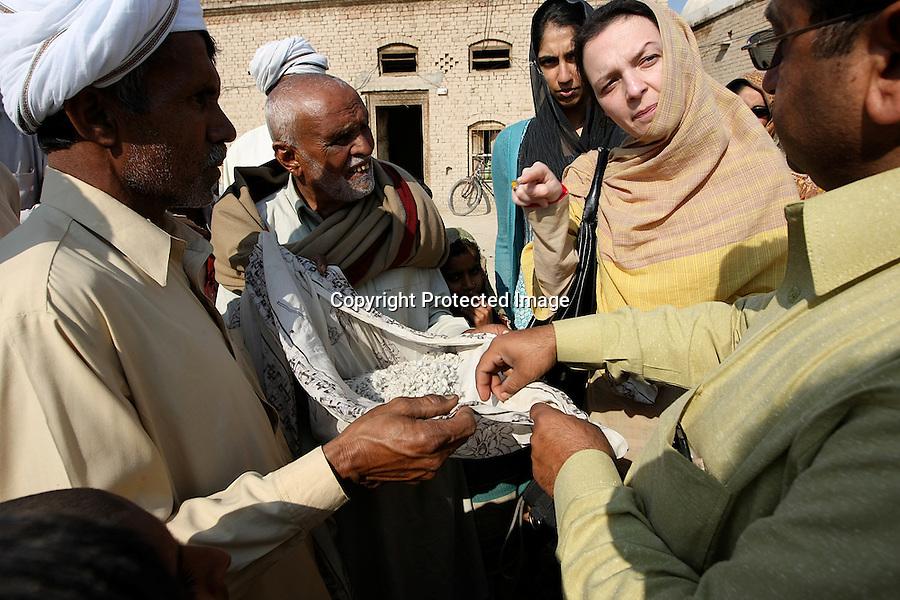 Farmers are explaining to Chairman Acid Survivors Foundation Ms Valerie Khan Yousafzai how they use acid to fertilize coton seeds. Around Muzzafar Garh, Pakistan-2009
