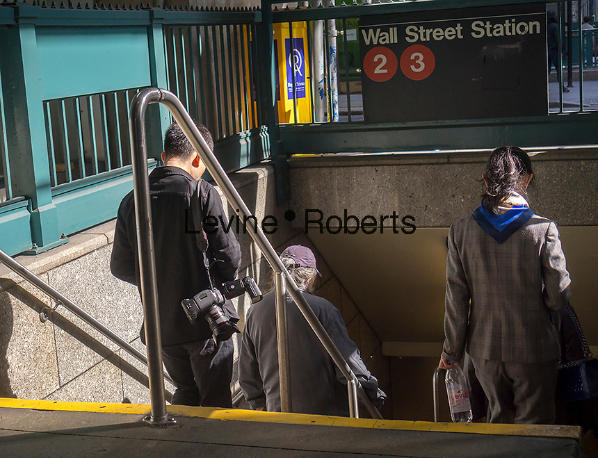 Travelers enter a Wall Street subway entrance in New York on Sunday, October 16, 2016. (© Richard B. Levine)