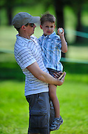 Bethesda, MD - June 29, 2014: Gary Woodland tosses this young fan a souvenir during final round of play at the Quicken Loans National at Congressional Country Club in Bethesda MD. (Photo by Phillip Peters/Media Images International)