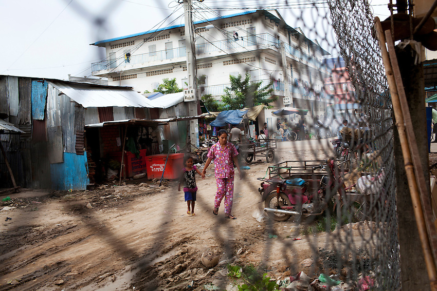 A garment factory worker walks with her child in a housing district near the Shen Zhou garment factory, in Phnom Penh, Cambodia, on September 14, 2011.