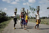 Children carry cans of water to a 'batteye' housing Haitian migrant cane-cutters on a sugar plantation in the Dominican Republic