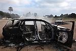 A destroyed car sits in a field while trash smolders in the background in Carthage suburb, Tunis, Tunisia, Jan. 16, 2011. Since the Tunisian President Zine El Abidine Ben Ali fled the country, rioting, looting and violence have engulfed some areas, especially at night. Members of Ben Ali's reviled wife's family, the Trabelsis, lived in Carthage, where one member of the family owned a car dealership. Cars throughout the area were burned and destroyed during rioting at night.