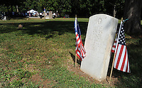 STAFF PHOTO ANDY SHUPE - The gravestone of Samuel Gregg, a relative of Lafayette Gregg, stands near a group of church members during a dedication ceremony Sunday, Sept. 21, 2014, for the Gehring Cemetery at Christian Life Cathedral in Fayetteville.