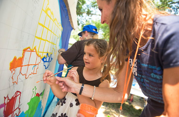 UNITED STATES - JULY 07:  Anna Boyles, 6, of Tennessee, is instructed by Marla Kozlak, of the Peace Corps, while painting a map of the world in the Peace Corps section of the Smithsonian Folklife Festival held on the National Mall.  This year's festival features the country of Colombia, Rhythm and Blues music, and the Peace Corps.  (Photo By Tom Williams/Roll Call)