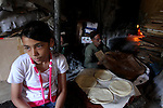 A Palestinian girl sits near the baker while he prepares loaves of bread at his traditional bakery in Gaza City on August 29,2010 . Photo by Ashraf Amra