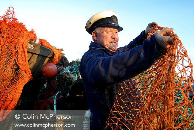 John Johnston, harbour master at the port of Eyemouth on Scotland's east coast sorts nets as he waits for the fishing fleet to arrive back in port with catches of cod, haddock, whiting and prawns. Proposals by scientists to ban fishing for cod, due to collapsing stocks meant that most boats found it increasingly uneconomical to continue to fish, putting at risk an estimated 20,000 jobs in the industry. The fall in fish catches was blamed on environmental factors and over fishing by Scottish and other European nation's fishermen.