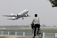 Chinese people watch airplanes outside the Beijing International Airport on May 30, 2005. Beijing, China.