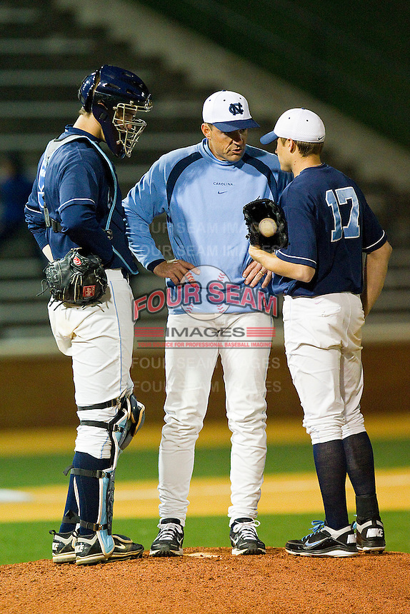 North Carolina Tar Heels assistant coach Scott Forbes #21 has a meeting on the mound with Patrick Johnson #17 and Jacob Stallings #5 during the game against the Wake Forest Demon Deacons at Gene Hooks Field on March 11, 2011 in Winston-Salem, North Carolina.  Photo by Brian Westerholt / Four Seam Images