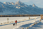 A young woman runs with her dog along a country road in Jackson Hole, Wyoming.