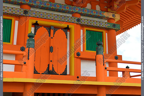 Architectural detail of Sanjunoto pagoda at Kiyomizu-dera Buddhist temple painted in bright orange with colorful ornaments. Kyoto, Japan.