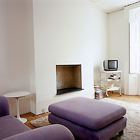 The living room has a minimal fireplace and is furnished with a matching purple sofa and ottoman