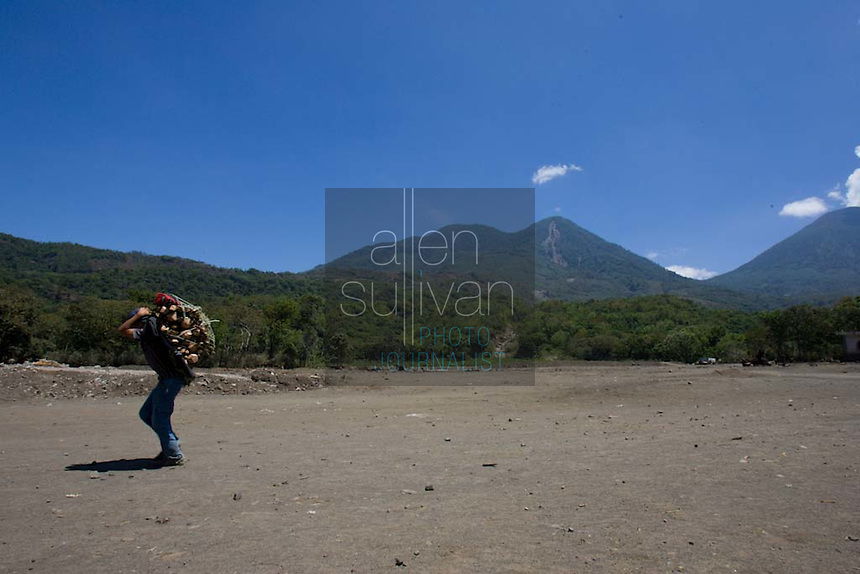A villager carries wood in an area of Panabaj, Guatemala on Saturday, March 17, 2007. A deadly mudslide was spawned by rains associated with Hurricane Stan in October 2005. Initially, up to 500 Tzujutil Maya villagers were believed to have been killed by the mudslide, which essentially  wiped away the town. The area pictured once featured many homes. Forensic anthropologists from the Fundación de Antropología Forense de Guatemala have been working to unearth the bodies of the missing and have recovered more than 100. They have also found the number of missing to be lower than originally thought, after many people were located in shelters or living in other towns after the disaster.