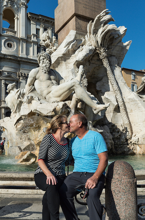 Tourist couple exchange a romantic kiss in front of the Fontana dei Quattro Fiumi located in the Piazza Navona, Rome, Italy