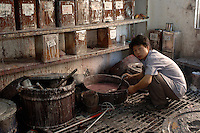 Worker at a paint factory in Shenzhen mixes paints that are used to color various plastic products, mostly silver and gold coloured electronics materiels. The specialised factory employs about 100 workers..