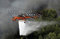 Pictured: A fire helicopter douses flames.<br /> Re: A forest fire has been raging in the area of Kalamos, 20 miles north-east of Athens in Greece. There have been power cuts, country houses burned and children camps evacuated from the area.