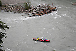 Robert Scott (bow) and Gordon Congdon run by a large log jam on Gataga River in northeast British Columbia.<br />