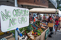A farmers hand-lettered chalk sign proclaim his organic non-GMO fruits and vegetables at a farmers market.