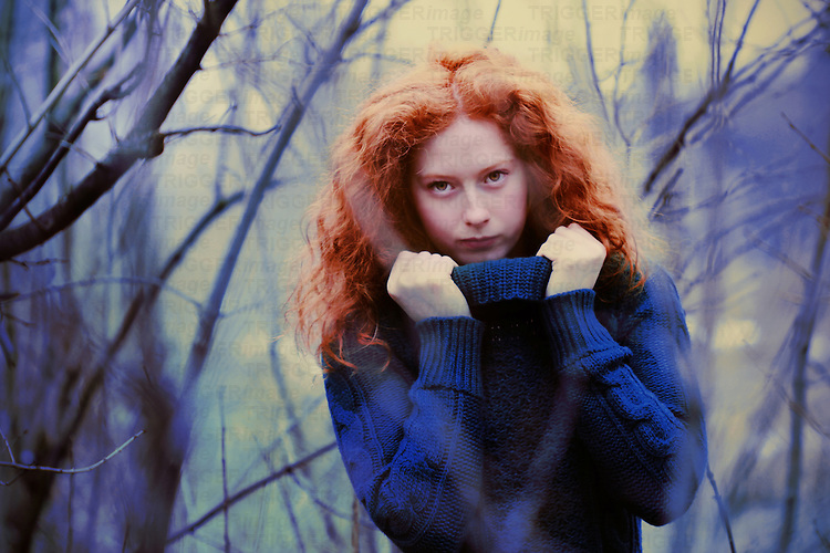 Female youth with curly red hair wearing a blue wool jumper and standing among branches.