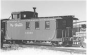 Side-end angle view of long caboose #04990, flying herald, peaking roof, at Alamosa.<br /> D&amp;RGW  Alamosa, CO  Taken by Richardson, Robert W. - 1/6/1949