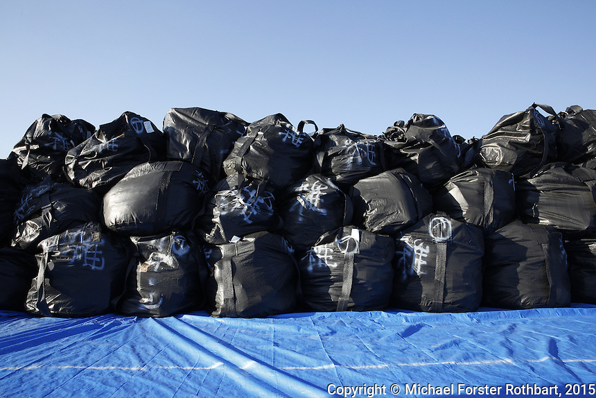 As towns in the Fukushima Exclusion Zone get decontaminated, scraped topsoil, organic waste and debris from demolished buildings with low-level radioactive contamination get loaded into heavy-duty cubic-meter bags. These bags pile up on worksites, roadsides and temporary storage fields across the Exclusion Zone. This storage site by the Yamadahama neighborhood in Naraha has meter bags stacked three high in pyramids of 192 bags; a total of 12,096 bags will occupy this site when it is full, and the field is one of dozens filling the floodplain beside the Kido river.<br /> <br /> &copy; Michael Forster Rothbart Photography<br /> www.mfrphoto.com &bull; 607-267-4893<br /> 34 Spruce St, Oneonta, NY 13820<br /> 86 Three Mile Pond Rd, Vassalboro, ME 04989<br /> info@mfrphoto.com<br /> Photo by: Michael Forster Rothbart<br /> Date:  10/5/2015<br /> File#:  Canon &mdash; Canon EOS 5D Mark III digital camera frame A28465