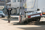 Mar. 13, 2011 - Kita-Ibaraki Japan - A man walks past vehicle is shown flipped over on the road two days after the 8.9 magnitude earthquake struck followed by a tsunami that hit the north-eastern region. The death toll is currently unknown with casualties that may run well into the thousands.