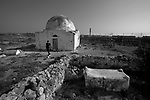 Muhammad walks near an old tomb in Hableh, close to the separation wall with Matan, seen in background. He has been visiting the tomb since childhood.