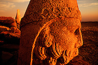 Close up detailof the stone sculpture of Zeus with Antiochos in the background as dawn breaks over the East Terrace. Nemrut Dag, Turkey.