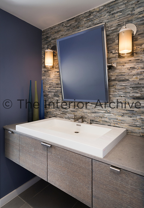 A contemporary blue bathroom with a washbasin set in a wall-mounted, stained wood cupboard unit. A mirror and two wall lights are fixed to a stone clad wall.