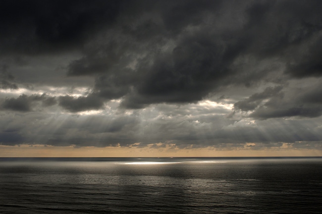 Sun coming through storm clouds on ocean